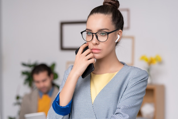 Задумчивая молодая бизнес-леди в синей клетчатой куртке в беспроводных наушниках держит телефон возле лица, думая о проекте