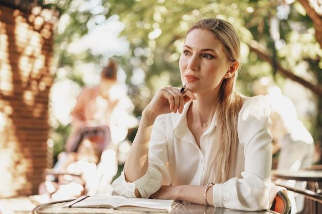 Задумчивый молодой предприниматель сидит в летнем кафе и делает заметки