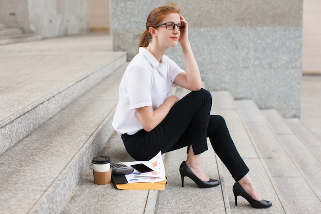 Pensive young businesswoman sitting on staircase