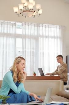 Задумчивая молодая бизнесвумен, работающая из дома из-за карантина и отвечающая на электронные письма от клиентов и коллег