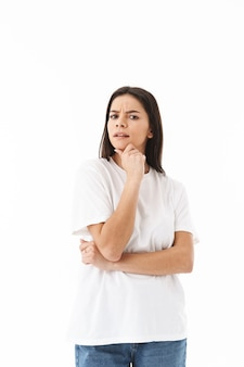 Pensive young casual woman standing isolated over white wall