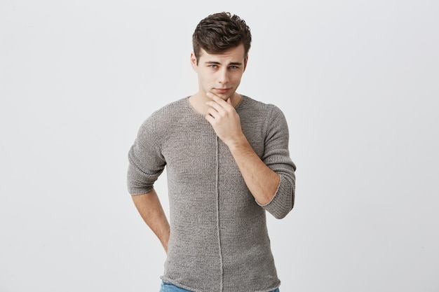 Pensive young caucasian guy wearing sweater touching his chin and looking ahead with faint smile. good-looking handsome man looking  with his blue eyes. human feelings and face expression.