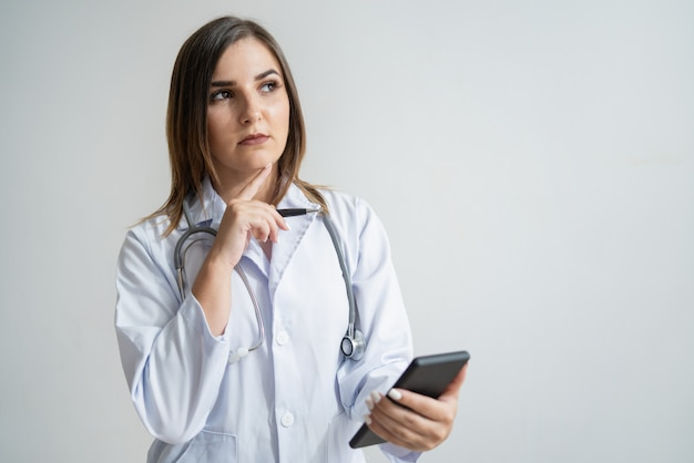 Pensive young caucasian woman in lab coat holding phone