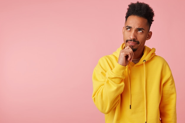 Pensive young dark skinned male with beard holding chin with raised hand and looking upwards with light smile, plotting something while standing in yellow sweatshirt