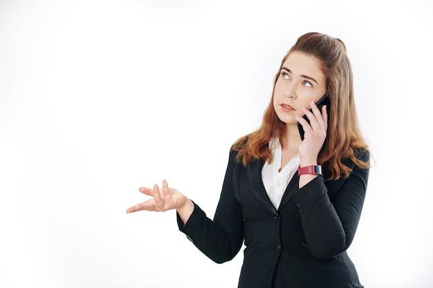 物思いにふける若い起業家が身振りで示すと電話で話しているときに見上げる、白で隔離