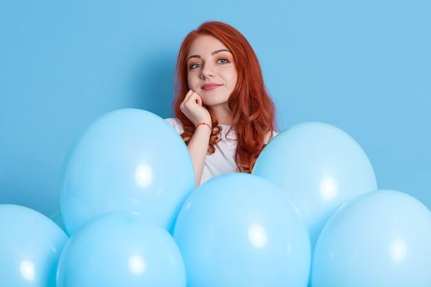 気球と青い壁に分離された白いシャツの物思いにふける若いヨーロッパの女の子。誕生日ホリデーパーティー。魅力的な生姜の女の子は、あごの下に拳を保ち、お祝いについて考えます。