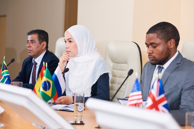 2人の異文化男性の間でテーブルに座っている同僚の報告を聞いているヒジャーブで物思いにふける若い女性代表