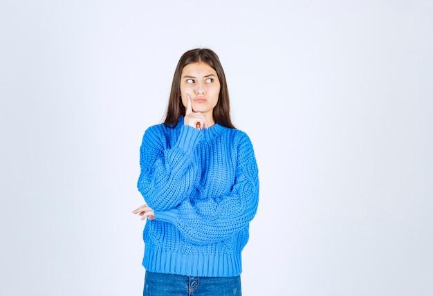 Задумчивая модель молодой девушки стоя и глядя.