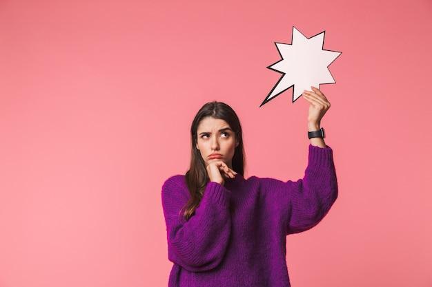 빈 연설 거품을 들고 핑크 이상 격리 서 스웨터를 입고 잠겨있는 어린 소녀