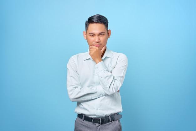 物思いにふける若いハンサムなビジネスマンはあごをこすり、青い背景の質問を考えています