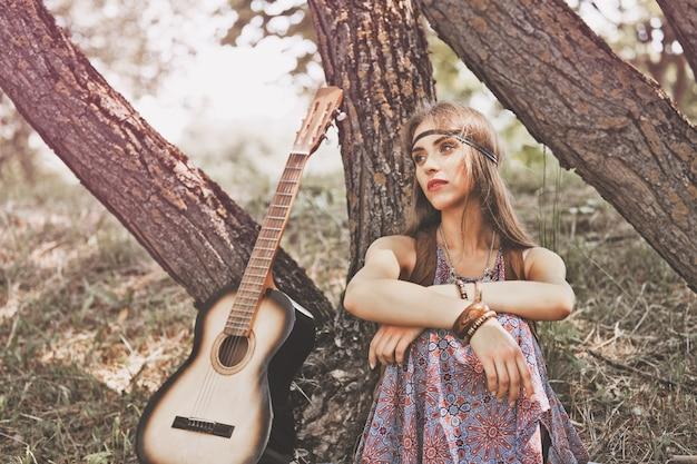 森の中の木の近くに座っている物思いにふける若いヒッピーの女性