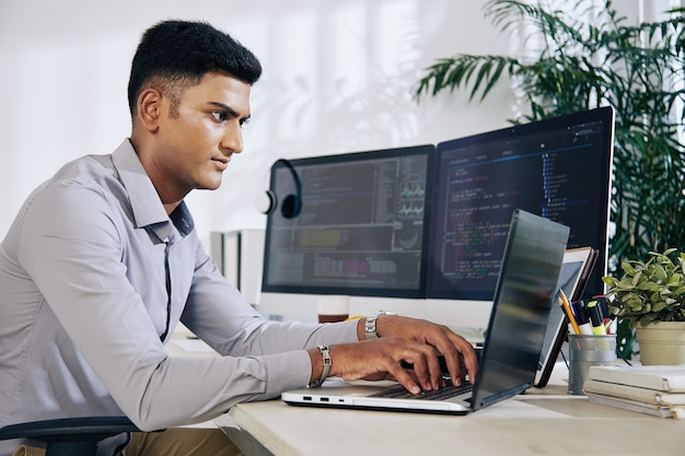 Pensive young indian programmer sitting at office desk with two monitors and typing on laptop