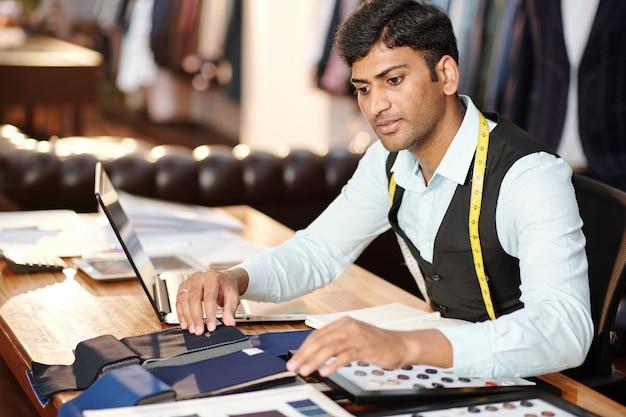 物思いにふける若いインドの仕立て屋がカタログをチェックし、スーツを作るための生地を選ぶ