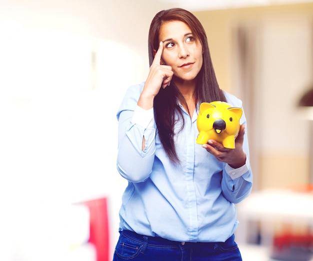 Задумчивый молодая дама держит желтый копилку