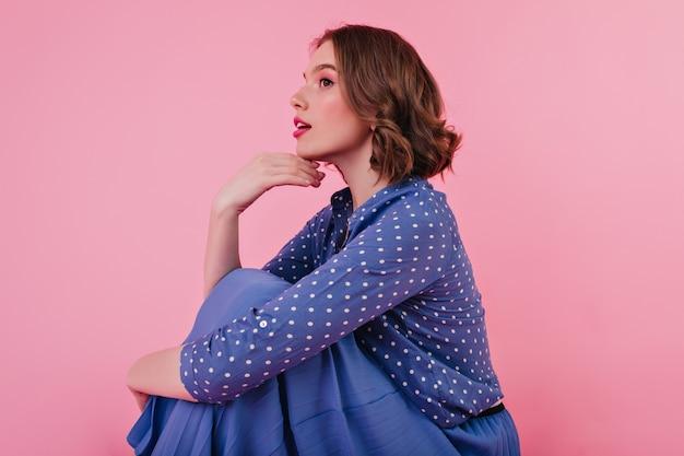Pensieroso giovane donna in gonna lunga seduta incantevole ragazza riccia in camicia elegante isolata sul muro rosa.