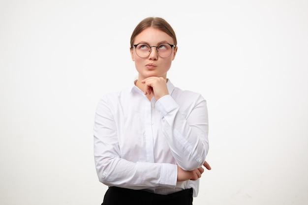白い背景の上に立っている間、眼鏡とフォーマルな服を着て、思慮深く上向きに見ながら上げられた手にあごを傾けて、ポニーテールの髪型を持つ物思いにふける若い素敵なブロンドの女性