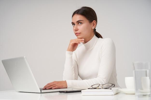 Задумчивая молодая милая темноволосая женщина с естественным макияжем, держащая подбородок поднятой рукой и задумчиво смотрящую вверх со сложенными губами, позирует над белой стеной