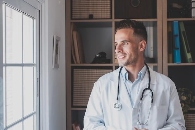 Задумчивый молодой кавказский врач-мужчина в белой медицинской форме смотрит в окно, размышляя или размышляя, серьезный мужчина gp планирует будущую карьеру или успех в медицине, визуализирует на рабочем месте, пишет