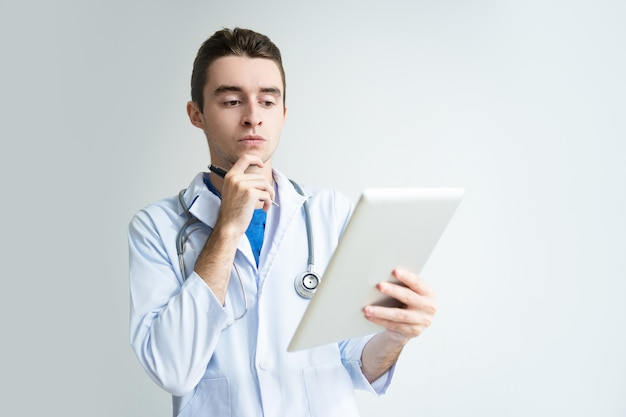 Pensive young male doctor using tablet computer
