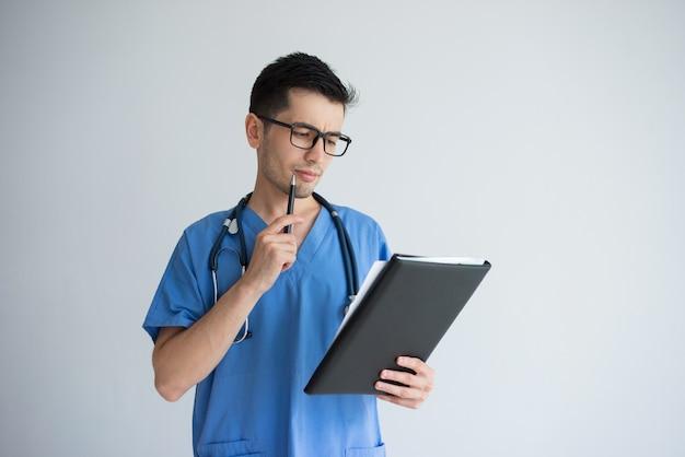 Giovane medico maschio pensieroso che scrive prescrizione medica. concetto di occupazione del medico