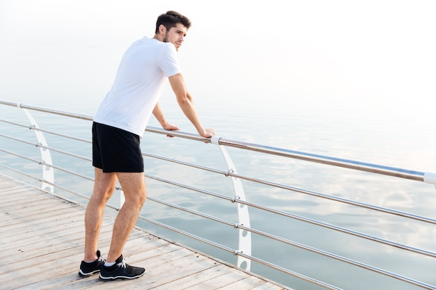 Pensive young man athlete resting after running standing on pier