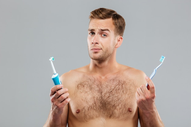 Pensive young man choosing toothbrush isolated on the gray wall