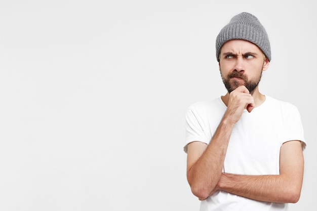 Pensive young man in grey hat, raised hand to face, touches his beard, looks dissatisfied suspiciously with disbelief