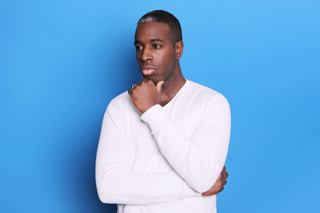 Pensive young man guy in casual white sweater posing isolated on blue background