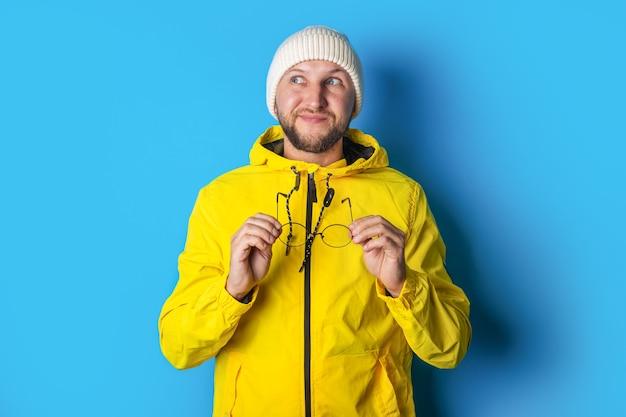 青の背景に黄色のジャケットで眼鏡を保持している物思いにふける若い男。