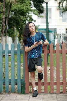 朝のランニングの後にイヤフォンで音楽を聴いて柵に寄りかかってスポーツ服を着た物思いにふける若い男