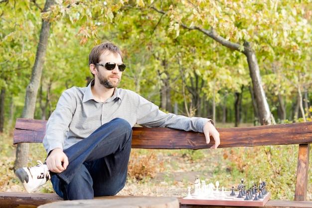 Задумчивый молодой человек в темных очках сидит на скамейке в лесу с шахматной доской рядом с ним и смотрит вдаль, глубоко задумавшись
