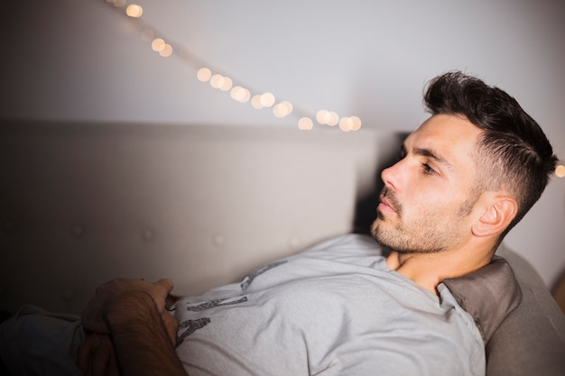 Pensive young man lying on sofa