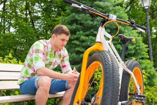 아름 다운 녹색 공원에서 지방 타이어와 자전거 근처 벤치에 앉아 잠겨있는 젊은 남자