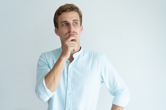 Pensive young man touching chin and looking away. Handsome guy thinking.
