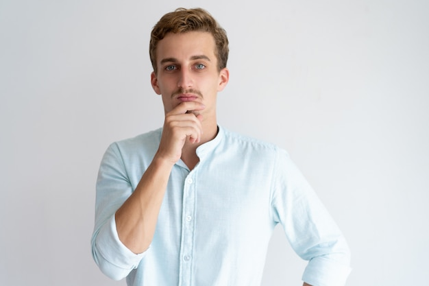 Pensive young man touching chin and looking at camera