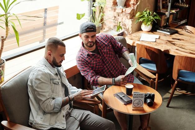 Задумчивый молодой человек с помощью цифрового планшета, планируя поездку с другом в кафе