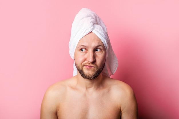 ピンクの背景に頭にタオルを持った物思いにふける若い男。