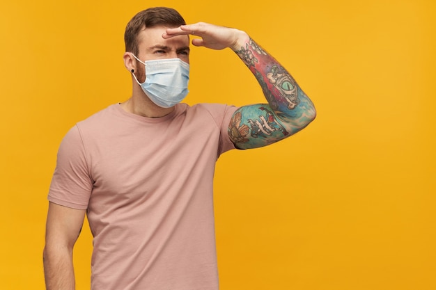 Pensive young man with beard and tattoo in pink tshirt and virus protective mask on face against coronavirus over yellow wall
