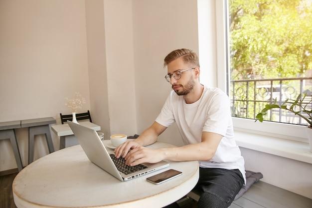 物思いにふける若い男がカフェで自分のコンピューターで作業し、テーブルに座って、現代のコンピューターでテキストを入力しています。ノートパソコン、コーヒー、スマートフォンがテーブルにあります。リモートワーク
