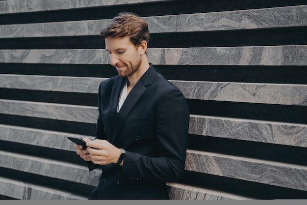 Задумчивый молодой офисный работник в формальном стильном костюме, стоящий на открытом воздухе, держа в руках мобильный телефон
