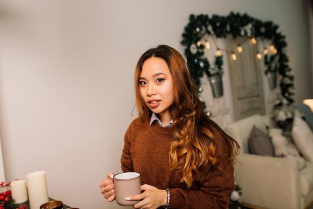 Задумчивая молодая довольно азиатская женщина с зажженными свечами в канун рождества, загадывая желание