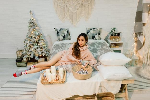 Задумчивая молодая довольно азиатская женщина с зажженными свечами в канун рождества загадывает желания