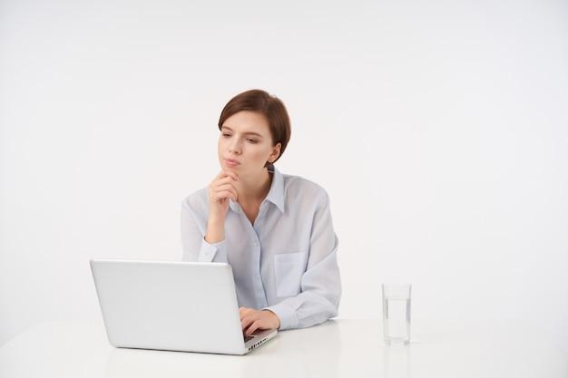 Pensieroso giovane donna dai capelli castani con taglio di capelli corto alla moda piegando le labbra mentre guarda pensieroso sul suo laptop e tiene il mento con la mano alzata, seduto su bianco