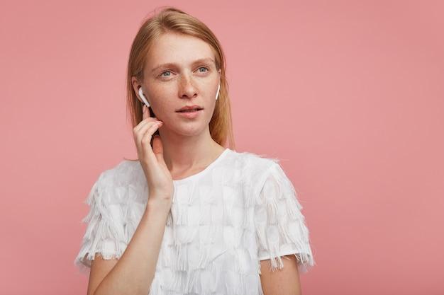 분홍색 배경 위에 포즈를 취하는 동안 우아한 티셔츠를 입고 강의를주의 깊게 듣는 동안 그녀의 이어폰에 손가락을 들고 잠겨있는 젊은 예쁜 빨간 머리 아가씨
