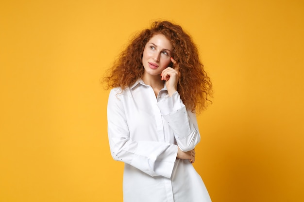 Pensive young redhead woman girl in casual white shirt posing isolated on yellow orange wall