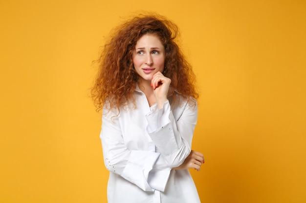 Задумчивая молодая рыжая девушка в повседневной белой рубашке позирует изолированной на желто-оранжевой стене