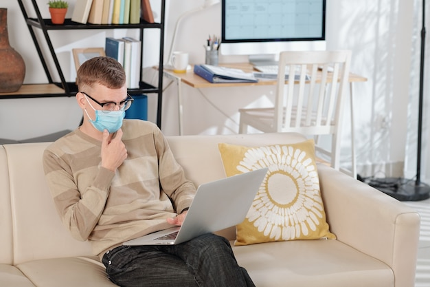 Задумчивый молодой инженер-программист в медицинской маске сидит на диване у себя дома и работает на ноутбуке