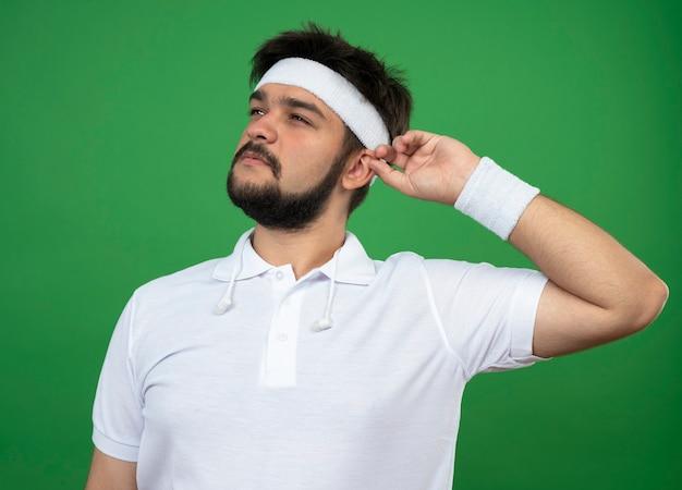 Pensieroso giovane sportivo guardando al lato indossando la fascia e il braccialetto che tiene l'orecchio isolato sul verde