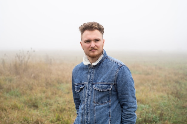 A pensive young stylish man with a mustache stands against gray misty nature background