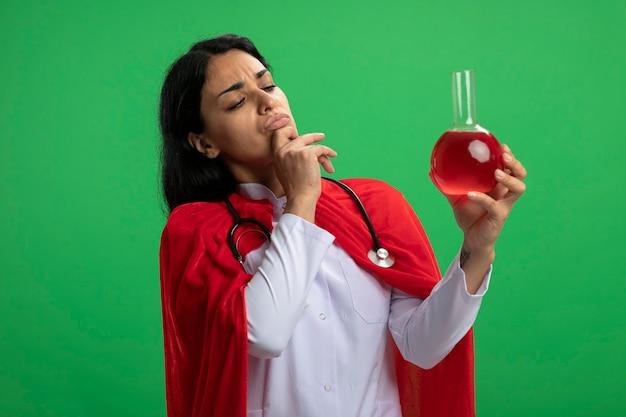 聴診器を持って医療用ローブを身に着けている物思いにふける若いスーパーヒーローの女の子は、緑に分離された赤い液体をつかんだあごで満たされた化学ガラス瓶を保持し、見ています